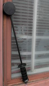 Hockey puck shaped impact tool leaning against a window